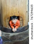 Small photo of NARA, JAPAN - APRIL 9 2017: Boy craw through the lucky pillar column hole at Todai-ji Daibutsu temple. It is a Buddhist temple complex which houses the world's largest bronze statue of Daibutsu.