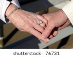 An older couple holds hands showing a wedding ring a brcelet and that love is in the air - stock photo