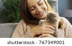 Stock photo charming young woman caressing a cute kitty cat while sitting on the sofa portrait shot inside 767349001