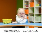 the child wears glasses  sits... | Shutterstock . vector #767387365