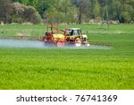 Tractor Spraying A Crop Field...