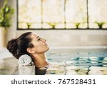 Small photo of Young beautiful woman enjoying summer holiday in swimming pool at resort hotel. Girl relaxing at hotel. Spa, retreat, relaxation concept. Beauty and body care