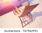 young woman in hat lying on a... | Shutterstock . vector #767562991