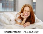 Small photo of Cute vivacious woman with a cheesy grin screwing up her eyes in mirth as she laughs at the camera while enjoying a book in bed