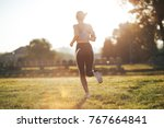 woman running during sunny... | Shutterstock . vector #767664841