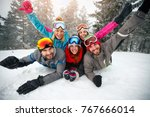happy skiers lying on snow and... | Shutterstock . vector #767666014