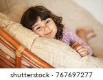 little curly girl resting on a... | Shutterstock . vector #767697277