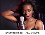 Beautiful african american girl on stage with microphone singing. Her hair is blowing back with wind effect and lit with red and blue lighting. - stock photo