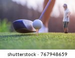 Small photo of wood driver in proper address of the woman golf player on tee off at golf club, ready to hit and impact away to the fairway ahead, with playermate waiting in background