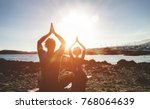 Stock photo couple doing yoga outdoor at sunrise in nature woman and man meditating together at morning time 768064639
