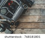 top view of work space photographer with digital camera in camera bag, flash, battery charger, cleaning kit, tripod, memory card, and camera accessory on wooden background