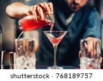 Stock photo close up details of barman pouring vodka cosmopolitan cocktail in martini glass 768189757