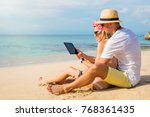 couple using tablet on the beach | Shutterstock . vector #768361435
