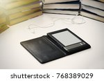 Small photo of Tab lies on a white table on a background of paper books. Headphones lie nearby.