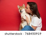 Stock photo young european brunette woman in white t shirt and jeans holding a dog shiba inu on plane red 768450919