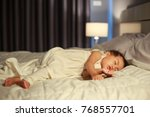 baby sleeping on bed after... | Shutterstock . vector #768557701