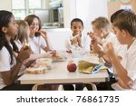 Stock photo students sitting at cafeteria table eating lunch 76861735