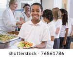 Stock photo students in cafeteria line with one holding his healthy meal and looking at camera 76861786