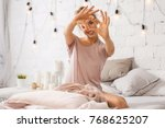Stock photo beautiful young woman sitting on bed and shows gesture heart with fingers portrait of smiling lady 768625207