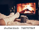 feet in woollen socks by the... | Shutterstock . vector #768707869