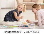mother with cute girl painting... | Shutterstock . vector #768744619