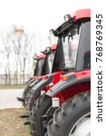 Small photo of Equipment for agriculture, machines presented to an agricultural exhibition. Tractors outdoors.