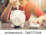 woman hand putting money bank... | Shutterstock . vector #768777334
