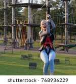 Small photo of fear of heights or acrophobia at zipline at high rophe course