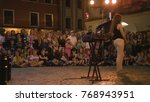 Small photo of Lublin, Poland - July 2017: Krystian Minda Sword Swallower Show in Lublin at night, during Festival Sztukmistrzow. Kneels in front of his assistant. The tool box on the first plan i out of focuse