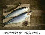Stock photo salted herring fish on an old wooden background with antique hand weights rustic style 768949417