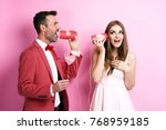 couple talking by tin can phone  | Shutterstock . vector #768959185