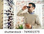 man is choosing glasses in...   Shutterstock . vector #769001575