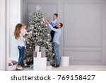 family decorating a christmas... | Shutterstock . vector #769158427
