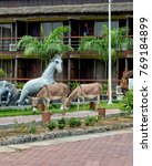 Small photo of Infrastructure of a luxury resort. Buildings, horses sculptures, avenue, walking donkeys. Modern African exterior. Travel and vacation in West Africa. Ghana, Volta, Ada - January 14, 2017