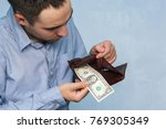 Small photo of Man gets money from the wallet. Hands close-up holding one dollar and a leather purse. Poverty and unemployment.