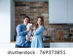 Stock photo young family pregnant woman and her partner or husband with dog and cat at kitchen 769373851