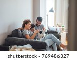 Stock photo mother father and son cuddling at home with their dog 769486327