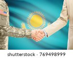 Small photo of American soldier in uniform and civil man in suit shaking hands with adequate national flag on background - Kazakhstan