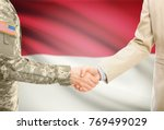 Small photo of American soldier in uniform and civil man in suit shaking hands with adequate national flag on background - Indonesia