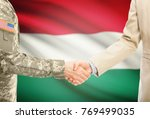 Small photo of American soldier in uniform and civil man in suit shaking hands with adequate national flag on background - Hungary