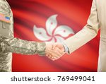 Small photo of American soldier in uniform and civil man in suit shaking hands with adequate national flag on background - Hong Kong