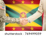 Small photo of American soldier in uniform and civil man in suit shaking hands with adequate national flag on background - Grenada