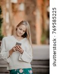 young blonde girl using phone.... | Shutterstock . vector #769585225