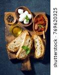 antipasti on a cutting board ... | Shutterstock . vector #769620325