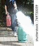 Small photo of Man holding afire extinguisher Spray fire