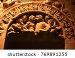 Small photo of Photography in sepia drawing and in semi-close-up of a sculptured stone. We perceive two central characters surrounded with sheets(leaves) of acanthus.