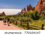 Small photo of Family walking in the Garden of the Gods park, Colorado Springs, CO, USA; whimsical red rock formations on the right; blue sky