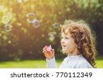 little girl blowing soap... | Shutterstock . vector #770112349