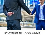 Small photo of Business concept hypocrisy, Young businessmen shake hands with fraudulent models.
