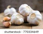 garlic on old wooden board. | Shutterstock . vector #770334649